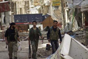 A Free Syrian Army fighter carries eggs as he walks with his comrades along a street lined with damaged shops and buildings in Deir al-Zor