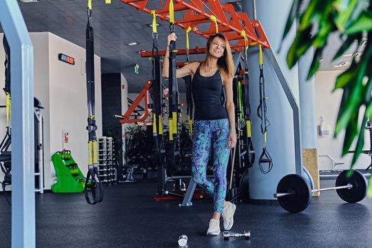 Sporty female posing near trx suspension strips stands in a gym club.