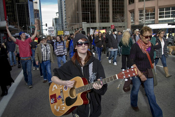 A protesters strums her guitar as she marches with Occupy Denver protesters through the streets of Denver