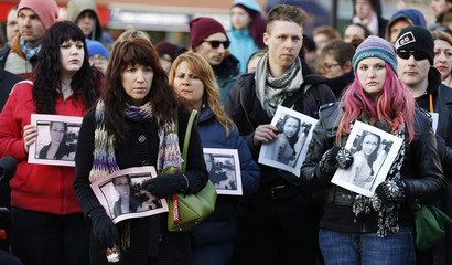 People hold photos of Rehtaeh Parsons during a memorial vigil at Victoria Park in Halifax