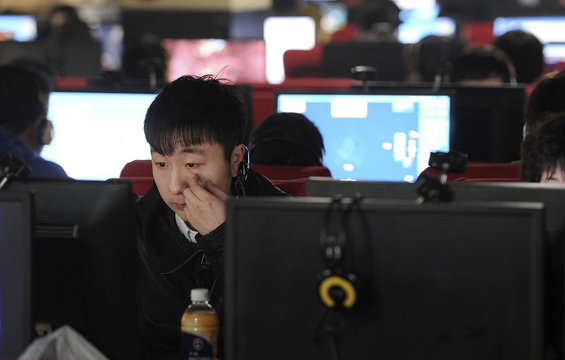 A man scratches his face as he uses a computer at an internet cafe in Hefei