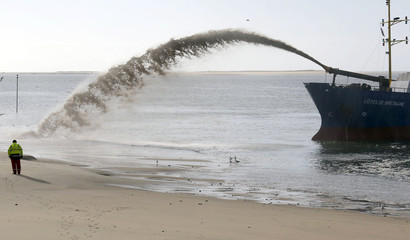 """A technician stands near an arc is formed as sand is projected from the """"Cote sde Bretagne"""" dredger onto the beach in Le Pyla on the Atlantic Ocean near Arcachon"""