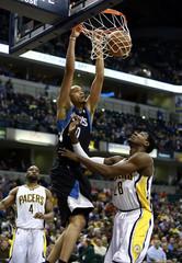 Minnesota's Chris Johnson dunks on  Indiana's Ian Mahinmi during an NBA basketball game in Indianapolis.