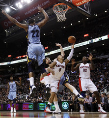 Raptors Bayless goes to the basket with  Davis against Grizzlies Gasol and Gay during their NBA basketball game in Toronto