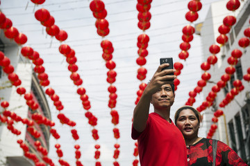 A man and woman wearing traditional red clothes celebrating the Chinese Lunar New Year take pictures of themselves in Bangkok