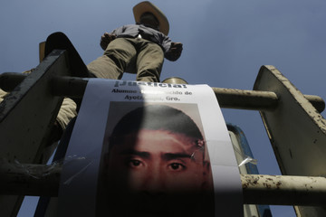 Man stands on top of a tractor as a picture of one of the 43 missing trainee teachers is seen during a protest in Mexico City