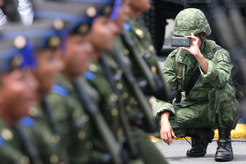 A soldier takes photos with mobile phone during a military parade celebrating Independence Day at Zocalo Square in downtown Mexico City