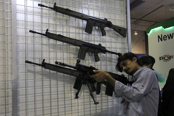 """A visitor checks a rifle on display, during the International Defence Exhibition and Seminar """"IDEAS 2014"""" in Karachi"""