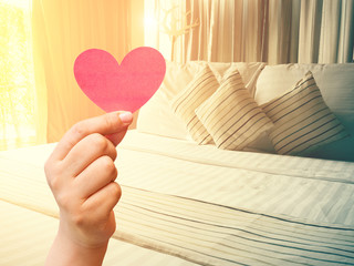 vintage bed and paper heart in hand with color tone effect