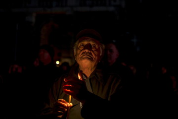A man holds a candle during a minute of silence in front of a destroyed military headquaters as Serbia marks the 16th anniversary of the NATO bombing campaign in Belgrade