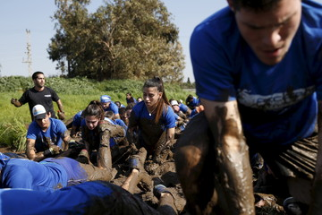 Israeli teenagers crawl through mud as they participate in an annual combat fitness training competition near Kibbutz Yakum, central Israel