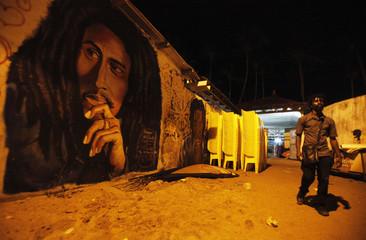 A man walks past a portrait of Bob Marley in Vridi's Village Rasta, Abidjan