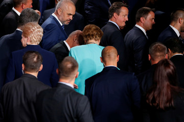 Merkel listens to Ghani as they depart after a family photo at the NATO Summit in Warsaw, Poland