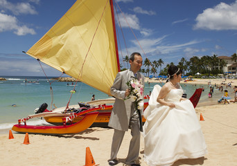 A Japanese couple walks past a sailing canoe on the beach after taking wedding pictures as two hurricanes approach the Hawaiian islands, in Honolulu, Hawaii.