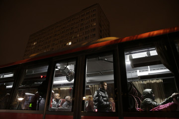 Migrants board a bus after their evacuation from the Lycee Jean Quarre, an empty secondary school occupied by hundreds of migrants and asylum seekers in the 19th district in Paris