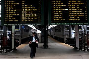 A New Jersey Transit commuter train conductor walks in the Hoboken station in Hoboken
