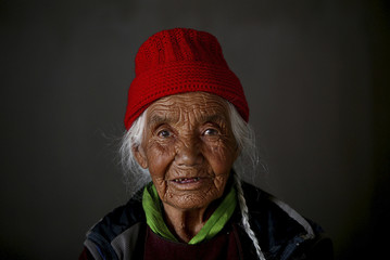A Buddhist woman sits as she waits to attend a yoga session inside a meditation centre on the outskirts of Leh