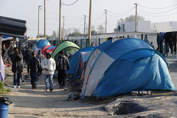 """Migrants walk in an alley near tents and makeshift shelters on the eve of the evacuation and dismantlement of the camp called the """"Jungle"""" in Calais"""