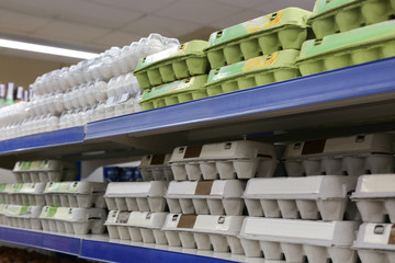 Eggs in cardboard boxes on shelves at supermarket