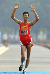 China's Wang Hao crosses the finish line to win the men's 20 km walk at the 16th Asian Games in Guangzhou