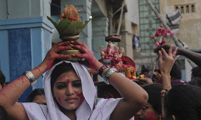 A woman carries a coconut on her head as an offering for the Hindu elephant god Ganesh at a Temple in Karachi