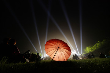 People watch a performance next to an umbrella at the 2011 Beijing Forest Music Festival near the Shuiguan section of the Great Wall on the outskirts of Beijing