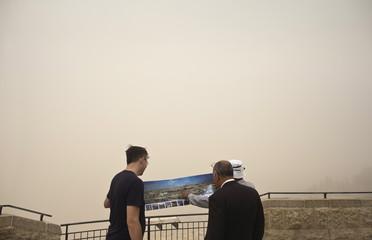 A tourist is shown a photograph of Jerusalem during a sandstorm