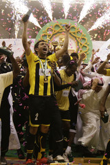 Al Itihad players celebrate with the Saudi King Abdullah Cup after defeating Al Hilal in the final match in Riyadh