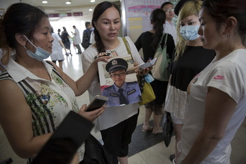 Zhang Yibi and women who accompany her, show a picture of her son Lei Chi, 21, a firefighter who is among those missing after the huge explosion at the port in Tianjin, China, as they visits a hospital looking for him