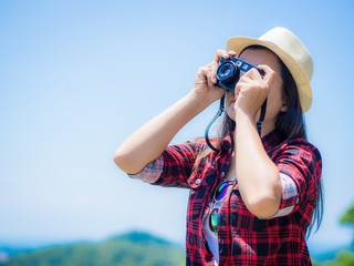 Outdoor summer lifestyle portrait of pretty young woman having fun in the jungle. Photographer making pictures in hipster style glasses and hat.