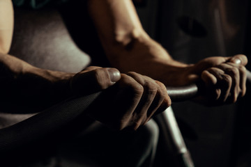 Hands of an athlete close-up, which does an exercise with a barbell. gym. biceps