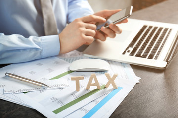 Man working with smartphone and documents. Tax concept