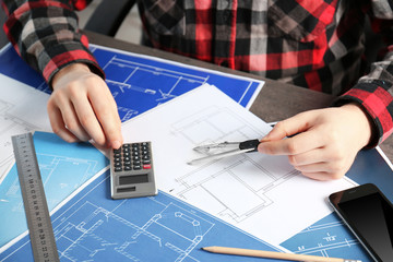Male engineer hands working with blueprints on table