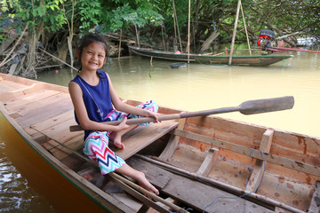 Asian girls are rowing with paddle on a wooden boat in a canal.