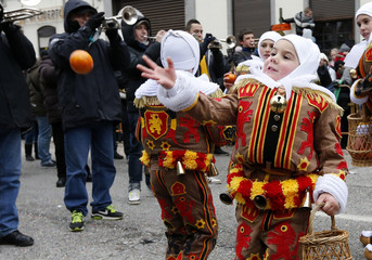 Noah Drugmand throws an orange as he takes part in his first parade with the Young Gilles of Binche during the carnival event in Binche