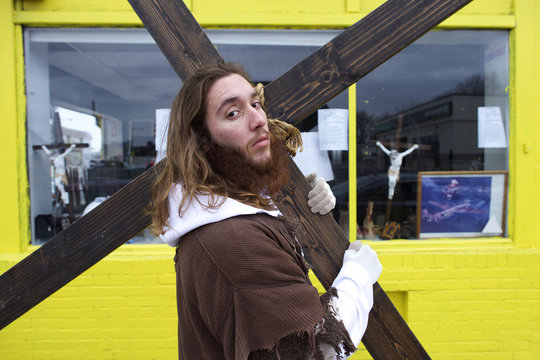 """Michael Grant, 28, """"Philly Jesus,"""" poses for a portrait in front of a store window featuring crucifixes with the 12 foot cross he carried 8 miles through North Philadelphia"""