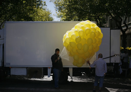 Demonstrators hold balloons to let go at the end of a protest, in front of the Health Ministry in Lisbon