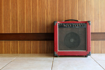 The old guitar amplifier with wooden walls.