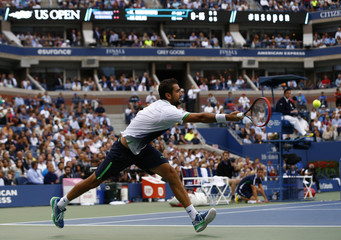 Cilic of Croatia hits a return to Nishikori of Japan during their men's singles final match at the 2014 U.S. Open tennis tournament in New York