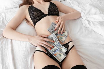 Sexy woman in lingerie with money on bed
