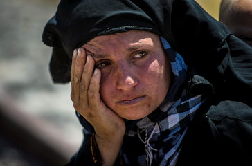 A woman rests after walking back to Tel Abyad town