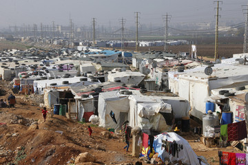 Syrian refugees walk at a refugee camp in Zahle in the Bekaa valley