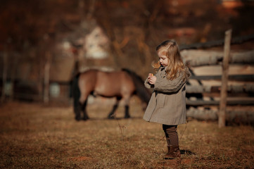 Portrait of little girl with her pony. Blonde, farm, jockey. Sunny backlight