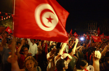 Anti-government protesters wave national flags during a demonstration in Tunis