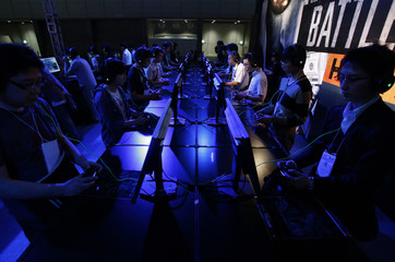 Visitors try out Electronic Arts' new game software Battlefield Hardline at Tokyo Game Show 2014 in Makuhari