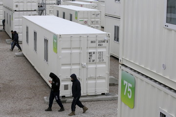 Migrants walk amidst shipping containers converted into homes at a state-run shelter near Calais, northern France