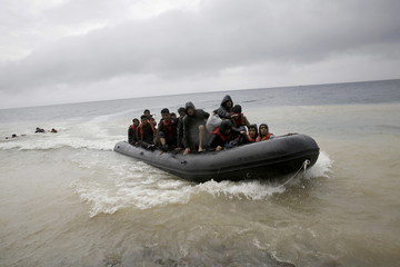 Afghan migrants arrive by a raft on the Greek island of Lesbos