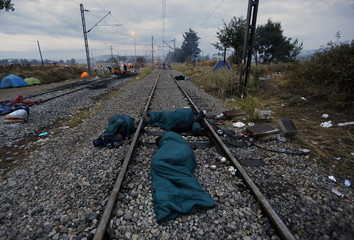 Syrian refugees sleep by a rail track at the Greek-Macedonian border, near the village of Idomeni
