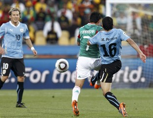Mexico's Barrera fights for the ball with Uruguay's Pereira during a 2010 World Cup Group A soccer match at Royal Bafokeng stadium in Rustenburg