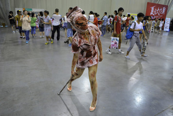 "A participant dressed as a ""Puppet Nurse"" from the video game ""Silent Hill"" poses for a photograph during a cartoon and comic book fair in Hefei"